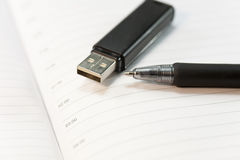 Pendrive or calendar?. A pen and a flash drive over a calendar Stock Image