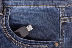 Pendrive in the pocket of blue jeans. Pendrive in the front pocket of blue jeans Stock Images