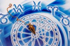 Pendulum and astrology. A gold pendulum lying on beautiful blue astrological background royalty free stock photo