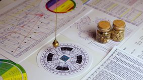 Pendulum for divination. Pendulum for tarot and astrological circle on the background of astrological charts, magical potions and astrological spreadsheets stock video