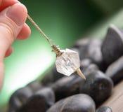 Pendulum. Hand with pendulum, tool for dowsing Stock Photos