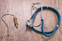 Pendulum and stethoscope on a wooden table Royalty Free Stock Image