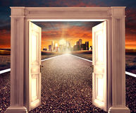 Pened door on empty road towards a distant city Royalty Free Stock Images