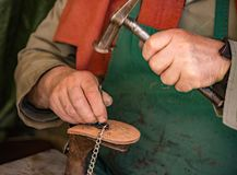 Traditional shoe maker works on heel insert Stock Photos