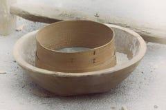 Peneira antiga da farinha em uma bacia de madeira imagens de stock