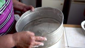 Peneirando a farinha através de uma peneira filme