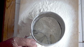 Peneirando a farinha através de uma peneira da mão filme