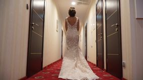 The penetration of the bride in a wedding dress with a train on the corridor stock footage