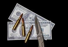 Pengar, ammunitionar och en kniv Royaltyfria Bilder