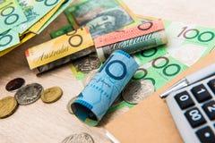 Pengar australiska dollar AUD, med anteckningsboken och räknemaskinen på Arkivbild