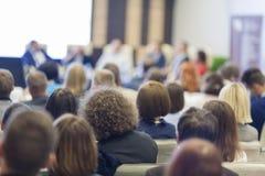 pengar för affärsräknemaskinbegrepp Folk på konferensen som lyssnar till värdshögtalare som sitter i Front On Stage Before The åh Royaltyfria Bilder