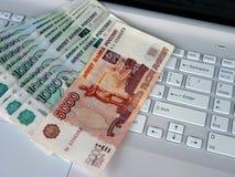 Pengar för datoren Arkivfoto