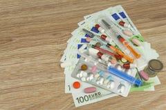 Pengar för dyr behandling Pengar och pills Preventivpillerar av olika färger på pengar Äkta eurosedlar Arkivbilder