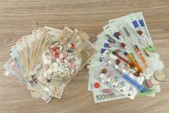 Pengar för dyr behandling Pengar och pills Preventivpillerar av olika färger på pengar Äkta eurosedlar Arkivbild