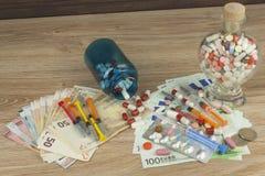 Pengar för dyr behandling Pengar och pills Preventivpillerar av olika färger på pengar Äkta eurosedlar Royaltyfria Foton