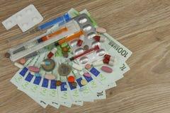 Pengar för dyr behandling Pengar och pills Preventivpillerar av olika färger på pengar Royaltyfri Foto