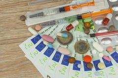 Pengar för dyr behandling Pengar och pills Preventivpillerar av olika färger på pengar Arkivfoto