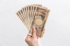 Pengar för japansk yen för affärskvinna holding10,000 i hand på vit bakgrund, japansk yen i begreppet av investeringen som är fin Royaltyfri Foto