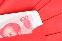 Pengar för kines eller för 100 Yuan sedlar i rött kuvert, som kines Arkivbilder