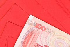 Pengar för kines eller för 100 Yuan sedlar i rött kuvert, som kines Royaltyfri Fotografi
