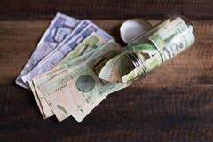 Pengar för saudierRiyalsedlar i krus och på trätabellen Royaltyfri Foto