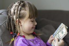 Pengar, finanser och folkbegrepp - le lilla flickan med dollarkassapengar Royaltyfri Fotografi