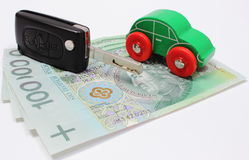 Pengar, grön leksakbil och tangentmedel Vit bakgrund Arkivfoto