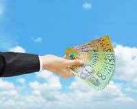 Pengar - hand som rymmer räkningar för australisk dollar (AUD) Fotografering för Bildbyråer