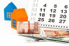 Pengar, hus och kalender Arkivbild