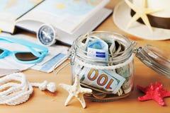 Pengar i den glass kruset på trätabellen Besparingar för sommarferier, semester, lopp och tur royaltyfri fotografi