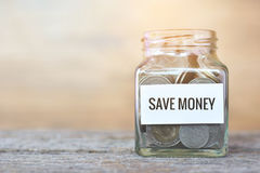 Pengar i en glass krus med ` sparar pengar`-ord Arkivbilder