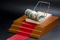 Pengar i en råttfälla på den röda mattan och svartbakgrunden Fotografering för Bildbyråer
