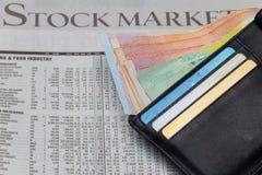 Pengar i ett fack över aktiemarknadtidningsbakgrund Royaltyfria Bilder