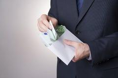 Pengar i ett kuvert i händerna av män Arkivbilder