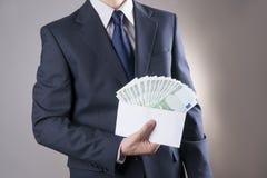 Pengar i ett kuvert i händerna av män Royaltyfri Foto