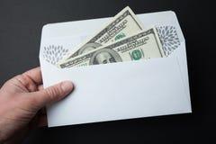 Pengar i ett kuvert på en svart bakgrund dollar f?r 100 bills arkivbild