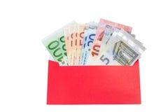 Pengar i ett ljust rött kuvert Arkivbild