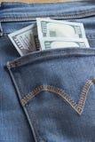 Pengar i fack av jeans Arkivfoto