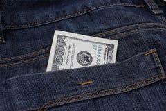 Pengar i flåsanden stoppa i fickan, 100 dollar i jeansfack Arkivbild