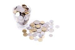 Pengar i glass mycket av mynt Arkivfoton