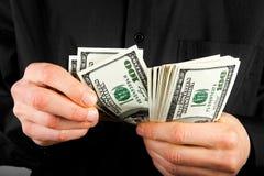 Pengar i händer Arkivbilder