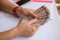 Pengar i handkvinnor äganderätt för home tangent för affärsidé som guld- ner skyen till Arkivfoto