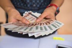 Pengar i handkvinnor äganderätt för home tangent för affärsidé som guld- ner skyen till Arkivfoton