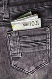 Pengar i jeansen stoppa i fickan Fotografering för Bildbyråer
