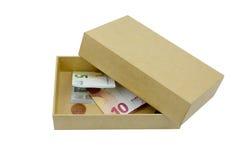 pengar i kartongen som isoleras på vit backgdround Arkivbild