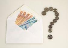 Pengar i kuvert och frågefläck från mynt Arkivfoton