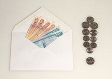 Pengar i kuvert och utropstecken från mynt Royaltyfria Bilder