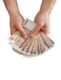 Pengar i mänsklig hand och vitbakgrund Arkivbild
