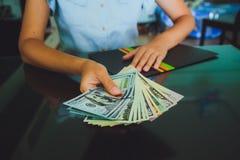 Pengar i mänskliga händer, kvinnor som ger dollar Fotografering för Bildbyråer
