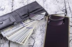 Pengar i plånbok, exponeringsglas och en smartphone Royaltyfri Fotografi